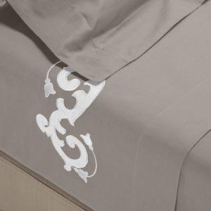 Completo di lenzuola in cotone percalle grigio rifinito con ricamo bianco e raso di cotone in applicazione su lenzuolo superiore e federe.