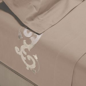 Completo di lenzuola in cotone percalle sabbia rifinito con ricamo sabbia con lino in applicazione su lenzuolo superiore e federe.