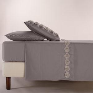 Completo lenzuola in morbido cotone impreziosito da fiori in macramè. Colore grigio scuro