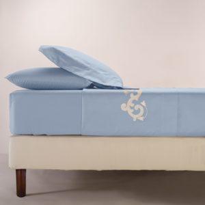 Completo di lenzuola in cotone pelleovo avio rifinito con ricamo bianco e raso di cotone in applicazione su lenzuolo superiore e federe.