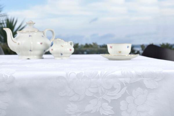 Tovaglia di fiandra di cotone bianco con disegno floreale rifinita con fine orlo a giorno
